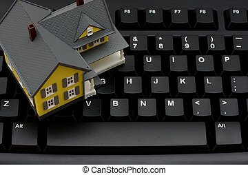 Real estate online - Computer keyboard with a model house,...