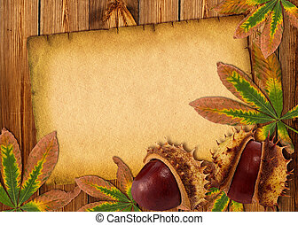 0ld paper background with autumn chestnuts and leaves on...