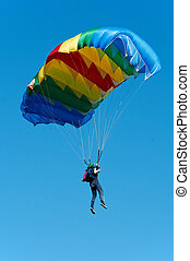 Parachute jumper - single parachute jumper against blue sky...