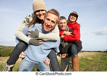 Two Couples Having Piggyback Ride In Autumn Landscape
