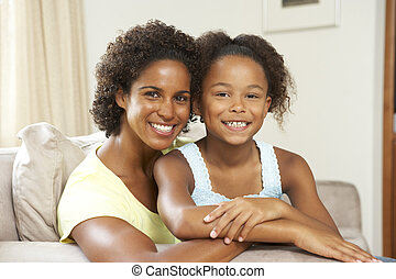 Mother And Daughter Relaxing On Sofa At Home