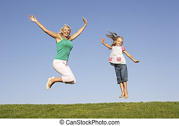 Senior woman with granddaughter jumping in air