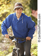 Portrait Of Young Man With Cycle In Autumn Park