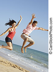 Young Couple Enjoying Beach Holiday Jumping In Air