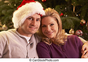 Couple Relaxing In Front Of Christmas Tree