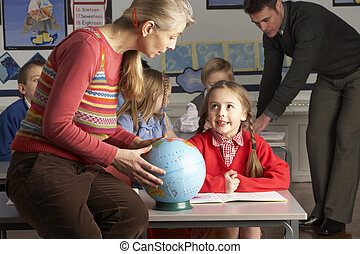 Teachers Giving Geography Lesson To Primary School Children...