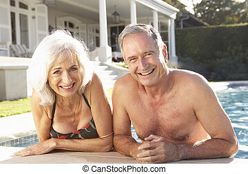 Senior Couple Relaxing by Outdoor Pool