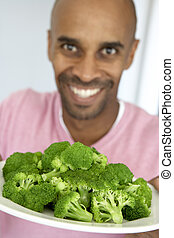 Middle Aged Man Holding A Plate Of Broccoli