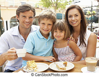 Young Family Enjoying Cup Of Coffee And Cake In Caf?...