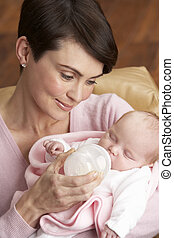 Portrait Of Mother Feeding Newborn Baby At Home