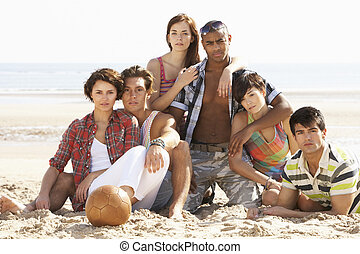 Group Of Friends Relaxing On Beach With Football Together