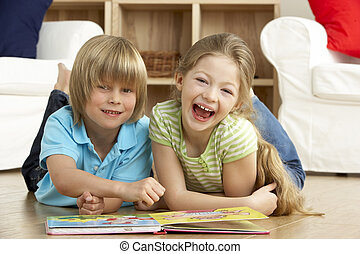 Two Young Children Reading Book at Home