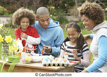 Family Painting Easter Eggs In Gardens