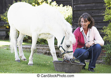 Farmers Wife Feeding Pony