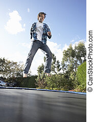 Young Man Jumping On Trampoline Caught In Mid Air