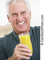Senior Man Holding A Glass Of Fresh Orange Juice, Smiling At...