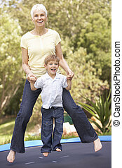 Grandmother And Grandson Jumping On Trampoline In Garden