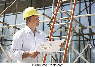 Architect Studying Plans Outside New Home