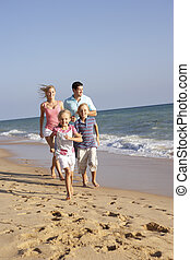 Portrait Of Running Family On Beach Holiday