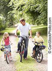 Father and children riding bikes in countryside