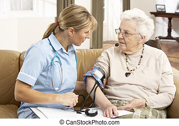 Senior Woman Ihaving Blood Pressure Taken By Health Visitor...