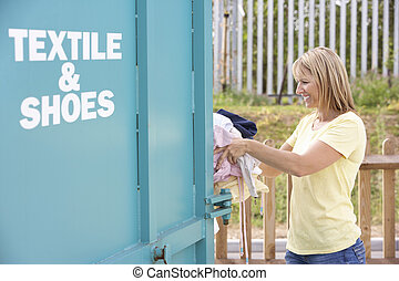 Woman At Recycling Centre Disposing Of Clothing