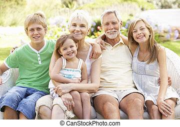 Grandparents And Grandchildren Relaxing In Garden