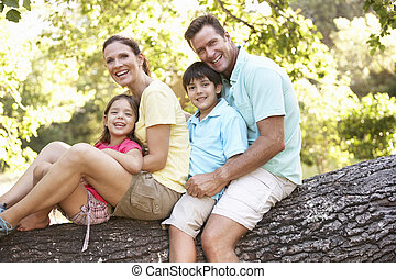 Family Sitting On Tree In Park