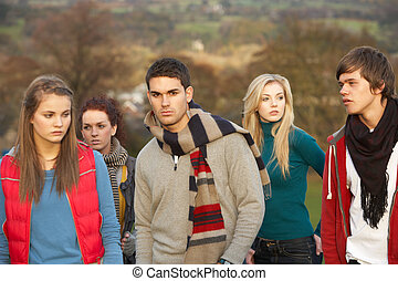 Teenage Boy Surrounded By Friends In Outdoor Autumn...