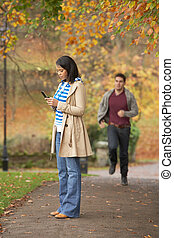 Teenage Girl Making Mobile Phone Call With Boyfriend Running Towards Her In Background