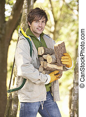 Man Outdoors In Autumn Woodland Gathering Logs