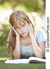 Female Teenage Student Studying In Park Looking Puzzled