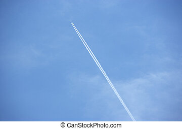 White Condensation Trail From A Jet As It Flies Across A...
