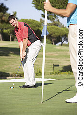 Male Golfer On Golf Course Putting On Green