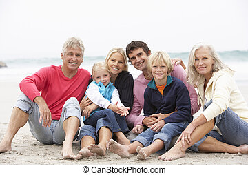 Three Generation Family Sitting On Winter Beach Together
