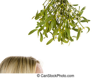 Woman standing under bunch of mistletoe against white...