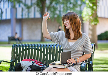 College girl waving hand - Young smiling college girl waving...