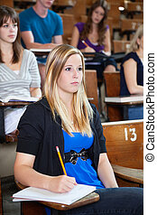 Students attending lecture - Students paying attention in...