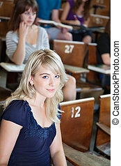 Portrait of college girl sitting in auditorium with...