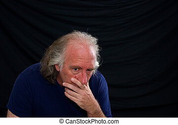man looking wide eyed and worried - An older caucasian man...