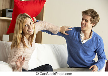 Young Couple Having Play Fight On Sofa