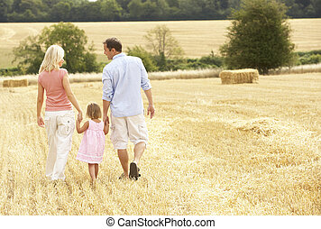 Family Walking Together Through Summer Harvested Field