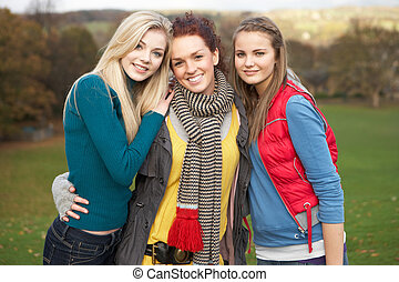 Group Of Three Teenage Female Friends In Autumn Landscape