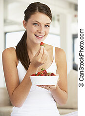 Young Woman Eating A Bowl Of Fresh Strawberries