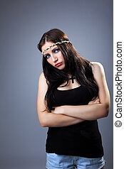 Grunge sad girl in tank top with cross on breast