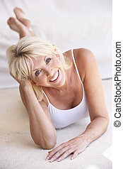 Middle age woman lying down strikes a pose