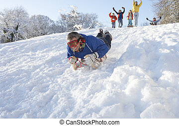 Man Sledging Down Hill With Family Watching