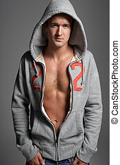 Studio Portrait Of Sexy Young Man Wearing Hooded Sweat Top