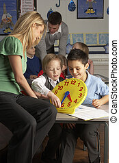 Female Teacher In Primary School Teaching Children To Tell...