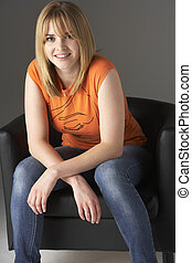 Studio Portrait Of Teenage Girl Sitting In Chair